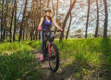 Uma jovem mulher - um atleta em um capacete que monta um Mountain bike fora da cidade, na estrada em uma floresta do pinho Fotografia de Stock Royalty Free