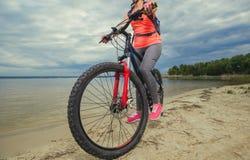 Uma jovem mulher, um atleta nas sapatas cor-de-rosa, caminhadas com um Mountain bike na manhã Foto de Stock
