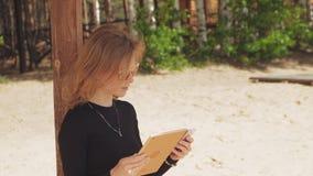 Uma jovem mulher usa uma tabuleta Conceito remoto do negócio video estoque
