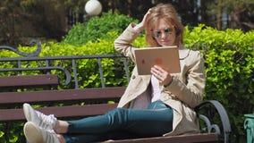 Uma jovem mulher usa uma tabuleta do computador Conceito remoto do neg?cio video estoque