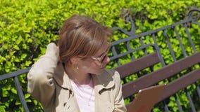 Uma jovem mulher usa uma tabuleta do computador Conceito remoto do neg?cio filme