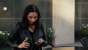 Uma jovem mulher usa um smartphone que senta-se em um café filme
