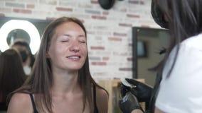 Uma jovem mulher veio ao salão de beleza para colorir e correção da sobrancelha filme