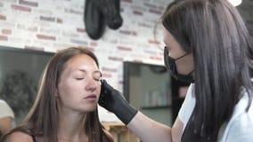 Uma jovem mulher veio ao salão de beleza para colorir e correção da sobrancelha video estoque