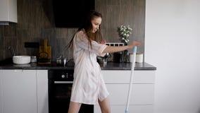 Uma jovem mulher vestida nos pijamas que dançam com um espanador na cozinha, uma senhora está tendo o divertimento e músicas do c filme