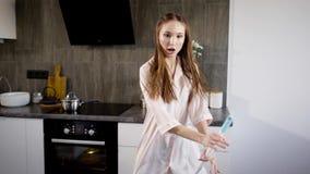 Uma jovem mulher vestiu-se nos pijamas engana ao redor durante uma dança com um espanador na cozinha, a senhora canta músicas vídeos de arquivo