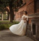 Uma jovem senhora está na parede de um castelo antigo que olha com esperança na distância Emoção que espera o longo Imagens de Stock Royalty Free