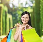 Uma jovem senhora feliz com os sacos de compras coloridos das lojas extravagantes Fotografia de Stock Royalty Free