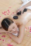 Uma jovem senhora que aprecia a massagem de pedra em termas Imagens de Stock Royalty Free