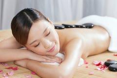 Uma jovem senhora que aprecia a massagem de pedra em termas Fotos de Stock