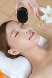 Uma jovem senhora que aprecia a massagem de pedra em termas Foto de Stock Royalty Free