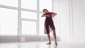 Uma jovem senhora que levanta uma sala coreográfica elegante em um estúdio da dança moderna video estoque