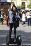 Uma jovem senhora que move sobre um segway nas ruas de Sevilha Fotos de Stock Royalty Free