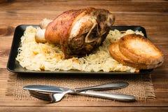 Uma junta roasted da carne de porco serviu com o chucrute no fundo de madeira Foto de Stock Royalty Free