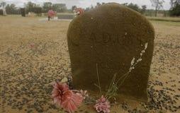 Uma lápide não marcado com o ANÚNCIO 1885 da data em um cemitério da sujeira imagens de stock royalty free