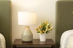 Uma lâmpada de mesa, um vaso com flores sobre uma mesa fotografia de stock