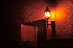 Uma lâmpada de rua em uma parede de tijolo vermelho que ilumina uma entrada em uma noite Imagem de Stock