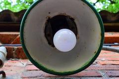 Uma lâmpada de rua gasto velha com uma ampola branca na luz do dia em uma rua do verão fotos de stock royalty free