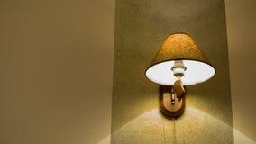 Uma lâmpada iluminada na parede com luz do sem-fim imagens de stock