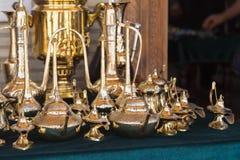 Uma lâmpada mágica do aladdin, chaleiras feitos a mão do ouro exibidas para a venda Loja de lembranças com os teakettles diferent imagens de stock royalty free