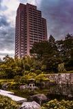 Uma lagoa no meio de tokyo com uma construção alta apenas conectada a ela um paraíso verde sob o céu azul foto de stock