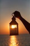 Uma lanterna com uma vela na mão no alvorecer Foto de Stock