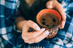 Uma laranja da xícara de café nas mãos imagem de stock