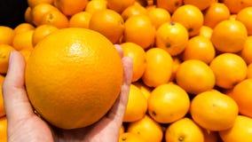 Uma laranja em uma mão com grupo de laranjas no supermercado imagens de stock royalty free