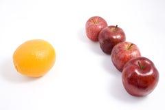 Uma laranja entre maçãs Imagens de Stock