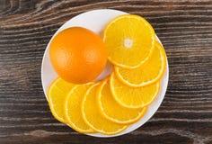Uma laranja inteira e fatias de laranjas no prato branco Fotografia de Stock