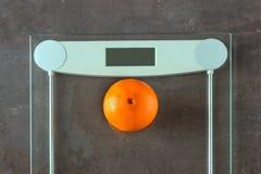 Uma laranja madura encontra-se nas escalas A perda de peso do conceito, nós Imagem de Stock Royalty Free