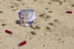 Uma lata de lata cercada por shell de espingarda gastos. Imagem de Stock Royalty Free