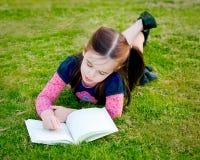 Uma leitura da menina na grama - de acima Fotografia de Stock Royalty Free
