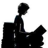 Uma leitura nova do menino ou da menina da silhueta do adolescente Fotos de Stock