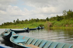 Uma linha de barcos azuis em um rio Foto de Stock Royalty Free