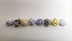 Uma linha de bolas de papel amarrotadas diferentes coloridas Fotografia de Stock Royalty Free