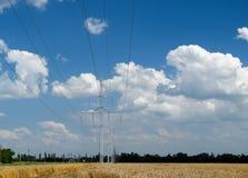 Uma linha de transmissão em um fundo de campos e de céu de trigo com nuvens foto de stock