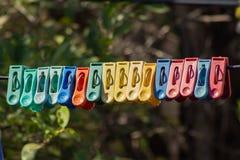 Uma linha longa de pregador de roupa que pendura em uma corda imagens de stock