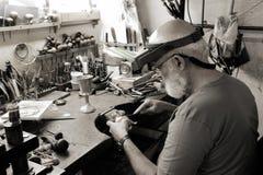 Uma loja muito velha do jewelery e um joalheiro no trabalho Imagens de Stock