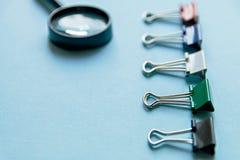 Uma lupa e uns clipes de papel coloridos em um fundo azul, tema do escritório foto de stock