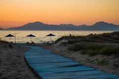 Uma luz - o passeio à beira mar azul conduz para baixo aos guarda-chuvas na praia, imagem de stock
