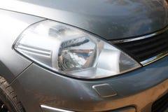Uma luz principal - close-up cinzento do carro. imagens de stock