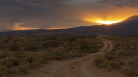 Uma luz video do por do sol das mostras do timelapse que incandesce alaranjada sobre a paisagem com uma estrada de terra que cond vídeos de arquivo