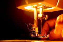 Uma máquina de costura que está sendo usada por um craftswoman indiano para rosquear uma parte de roupa imagens de stock