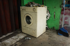 Uma máquina de lavar branca abandonada e não utilizada com porta da rua perto da parede verde e de uma vassoura Depok recolhido f Foto de Stock