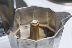 Uma máquina do café do geyser está no fogão bonde É visível porque o café pronto sob a pressão derrama para fora no recipiente fotografia de stock