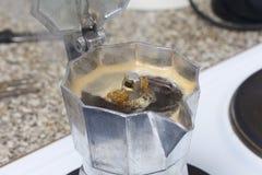 Uma máquina do café do geyser está no fogão bonde É visível porque o café pronto sob a pressão derrama para fora no recipiente fotos de stock