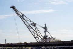 Uma máquina escavadora enorme sobrecarrega nas descargas balança do trem descarregado da mina contra um céu azul claro Conceito fotos de stock