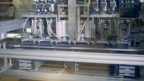 Uma máquina industrial está levantando células solares e está pondo-as na correia transportadora em seguido filme