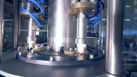 Uma máquina põe tampões sobre garrafas filme
